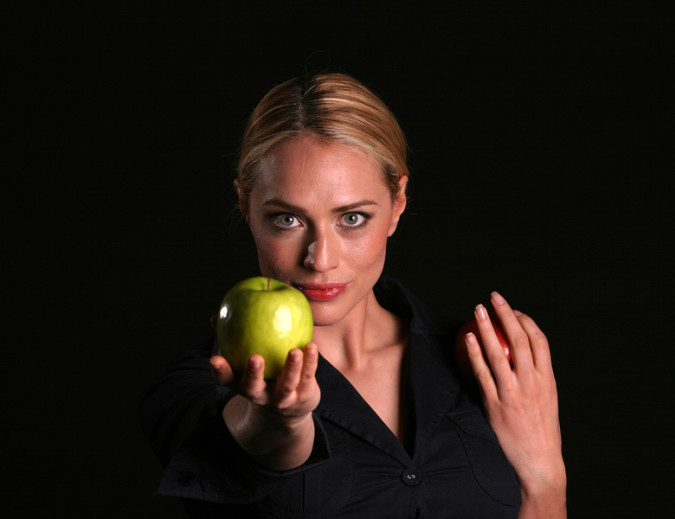 a healthy fit woman hands a fresh green apple to YOU the viewer