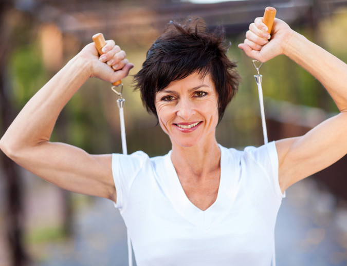 happy middle aged woman workout with jumping rope