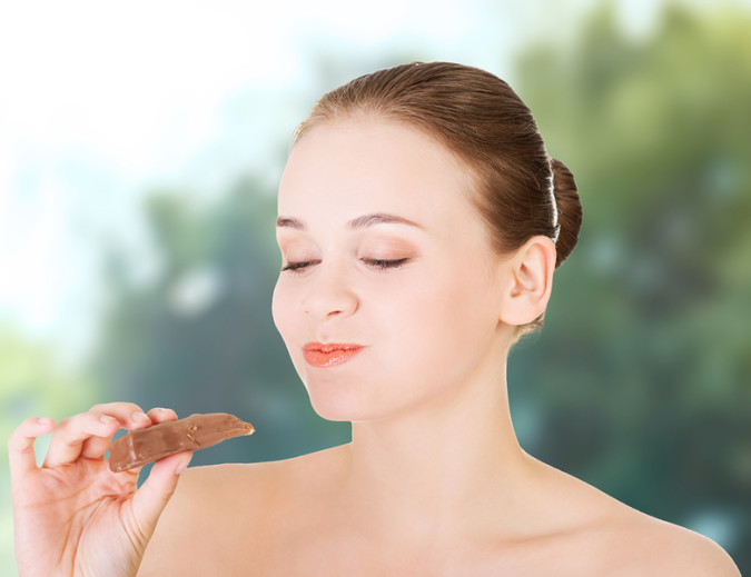 Beautiful young woman eating a chocolate bar.